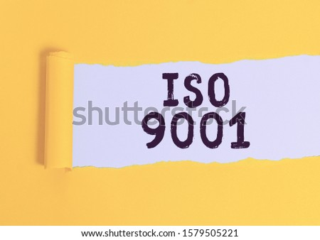 Writing note showing Iso 9001. Business photo showcasing designed help organizations to ensure meet the needs of customers Cardboard which is torn placed above a wooden classic table.