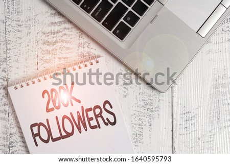 Writing note showing 200K Followers. Business photo showcasing number of individuals who follows someone in Instagram Top trendy metallic laptop blank spiral notepad lying on wooden table.