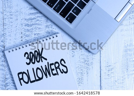 Writing note showing 300K Followers. Business photo showcasing number of individuals who follows someone in Instagram Top trendy metallic laptop blank spiral notepad lying on wooden table.