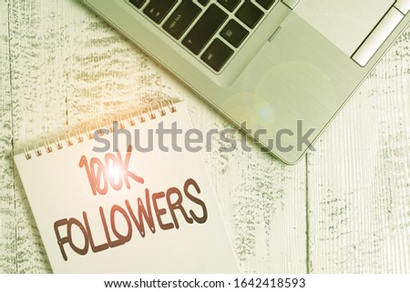 Writing note showing 100K Followers. Business photo showcasing number of individuals who follows someone in Instagram Top trendy metallic laptop blank spiral notepad lying on wooden table.