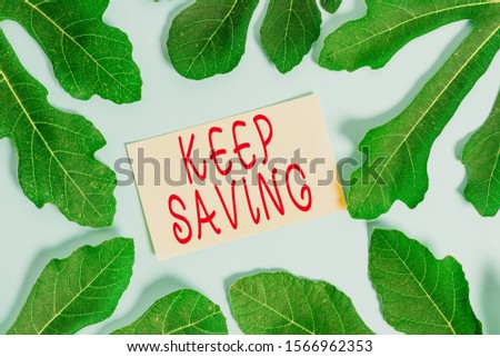 Writing note showing Keep Saving. Business photo showcasing keeping money in an account in a bank or financial organization Leaves surrounding notepaper above empty soft pastel table.