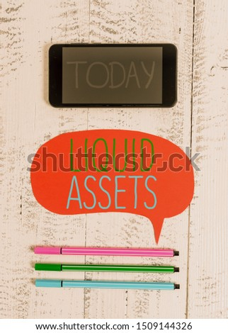 Writing note showing Liquid Assets. Business photo showcasing Cash and Bank Balances Market Liquidity Deferred Stock Smartphone cell pens blank colored speech bubble wooden background. #1509144326