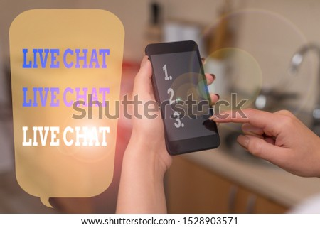 Writing note showing Live Chat Live Chat Live Chat. Business photo showcasing talking with showing friends relatives online woman using smartphone and technological devices inside the home.