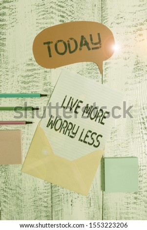 Writing note showing Live More Worry Less. Business photo showcasing Have a good attitude motivation be careless enjoy life Envelop speech bubble paper sheet ballpoints notepads wooden background.