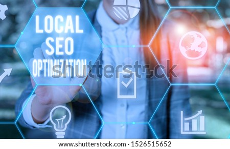 Writing note showing Local Seo Optimization. Business photo showcasing increase Search Visibility to Rank on Top list Female human wear formal work suit presenting smart device.