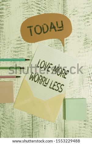 Writing note showing Love More Worry Less. Business photo showcasing Have a good attitude motivation be lovable enjoy life Envelop speech bubble paper sheet ballpoints notepads wooden background.