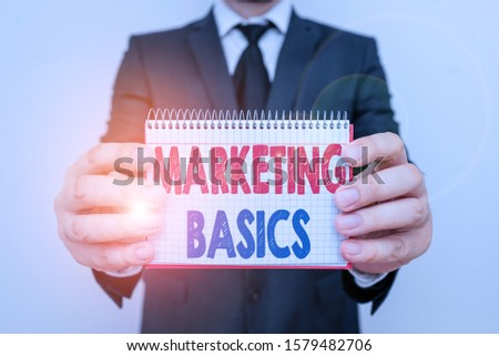Writing note showing Marketing Basics. Business photo showcasing activities a company takes to promote and sell products Male human wear formal work suit with office look hold book.
