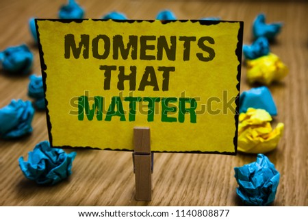 Writing note showing Moments That Matter. Business photo showcasing Meaningful positive happy memorable important times Paperclip grip yellow page with text woody floor blue and yellow lob. #1140808877