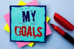 Writing note showing  My Goals. Business photo showcasing Goal Aim Strategy Determination Career Plan Objective Target Vision written on Sticky Note Paper on the Plain background Marker next to it.