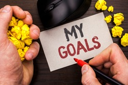 Writing note showing  My Goals. Business photo showcasing Goal Aim Strategy Determination Career Plan Objective Target Vision written by Man on Note Paper Holding Marker on Wooden background Mouse.