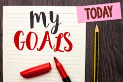 Writing note showing  My Goals. Business photo showcasing Goal Aim Strategy Determination Career Plan Objective Target Vision written on Notebook Paper on the Wooden background Today Marker Pencil.