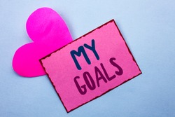 Writing note showing  My Goals. Business photo showcasing Goal Aim Strategy Determination Career Plan Objective Target Vision written on Pink Sticky Note Paper on the Plain background with Heart.