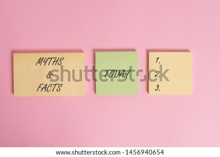 Writing note showing Myths And Facts. Business photo showcasing usually traditional story of ostensibly historical events Close up front view three multicolor blank notepads colored background.