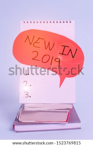 Writing note showing New In 2019. Business photo showcasing what will be expecting or new creation for the year 2019 Spiral notebook speech bubble stacked old books cool pastel background. #1523769815