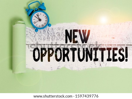 Writing note showing New Opportunities. Business photo showcasing exchange views condition favorable for attainment goal Alarm clock and torn cardboard on a wooden classic table backdrop.