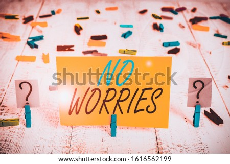 Writing note showing No Worries. Business photo showcasing an expression used to say that everything is all right Crumbling sheet with paper clips placed on the wooden table.
