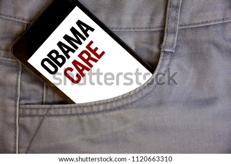 Writing note showing  Obama Care. Business photos showcasing Government Program of Insurance System Patient ProtectionConcept on cell phone on jean pocket white screen black and red letters.