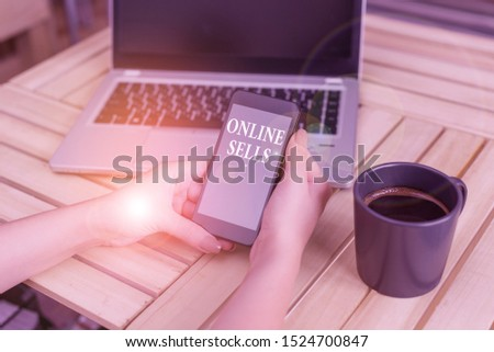 Writing note showing Online Sells. Business photo showcasing sellers directly sell goods or services over the Internet woman with laptop smartphone and office supplies technology.