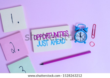 Writing note showing Opportunities Just Ahead. Business photo showcasing Advantageous circumstances Perseverance pays off Blank notepads marker rubber band alarm clock clip colored background.