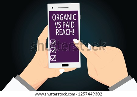 Writing note showing Organic Vs Paid Reach. Business photo showcasing Increasing followers naturally or by paying for it analysis Hands Holding Pointing Smartphone Blank Color Screen.
