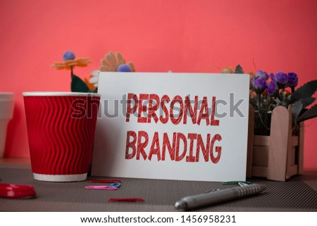 Writing note showing Personal Branding. Business photo showcasing Practice of People Marketing themselves Image as Brands Flowers and writing equipments sheet above textured backdrop.
