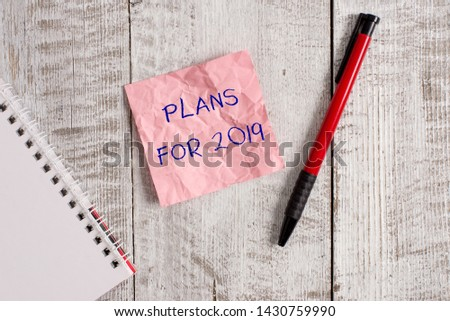 Writing note showing Plans For 2019. Business photo showcasing an intention or decision about what one is going to do Wrinkle paper notebook and stationary placed on wooden background. #1430759990