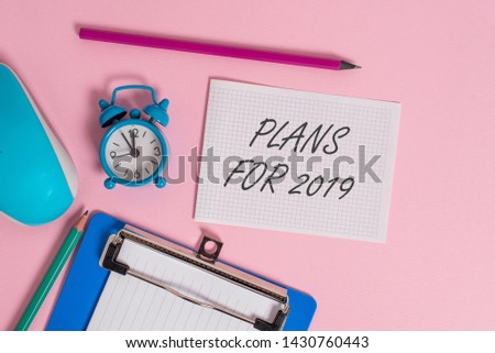 Writing note showing Plans For 2019. Business photo showcasing an intention or decision about what one is going to do Alarm clock clipboard paper sheets mouse markers colored background. #1430760443