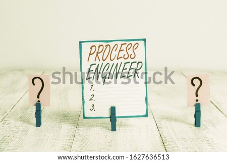 Writing note showing Process Engineer. Business photo showcasing responsible for developing new industrial processes Crumbling sheet with paper clips placed on the wooden table.