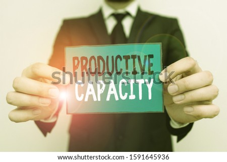 Writing note showing Productive Capacity. Business photo showcasing the maximum possible output of a production plant Male human wear formal work suit with office look hold book.