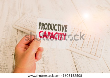 Writing note showing Productive Capacity. Business photo showcasing the maximum possible output of a production plant Man holding colorful reminder square shaped paper wood floor.
