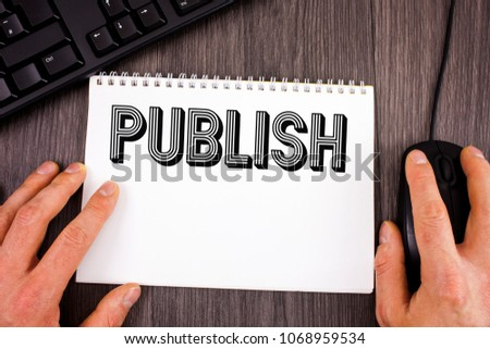 Writing note showing  Publish. Business photo showcasing Make information available to people Issue a written product written on Notepad on wooden background Keyboard and Mouse next to it. #1068959534