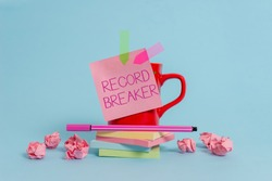 Writing note showing Record Breaker. Business photo showcasing someone or something that beats previous best result Coffee cup pen note banners stacked pads paper balls pastel background.