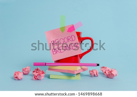 Writing note showing Record Breaker. Business photo showcasing someone or something that beats previous best result Coffee cup pen note banners stacked pads paper balls pastel background. #1469898668