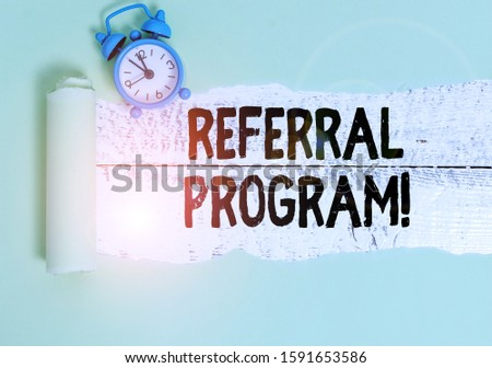 Writing note showing Referral Program. Business photo showcasing internal recruitment method employed by organizations Alarm clock and torn cardboard on a wooden classic table backdrop.