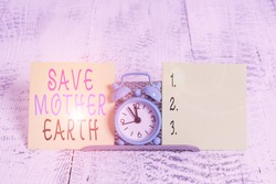 Writing note showing Save Mother Earth. Business photo showcasing doing small actions prevent wasting water heat energy Mini blue alarm clock standing above buffer wire between two paper.