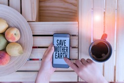 Writing note showing Save Mother Earth. Business photo showcasing doing small actions prevent wasting water heat energy woman with laptop smartphone and office supplies technology.