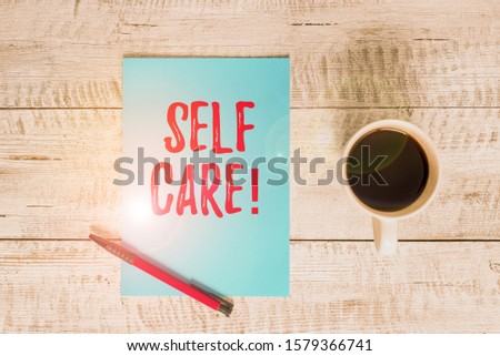 Writing note showing Self Care. Business photo showcasing practice of taking action preserve or improve ones own health Stationary placed next to a cup of black coffee above the wooden table.