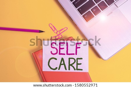 Writing note showing Self Care. Business photo showcasing practice of taking action preserve or improve ones own health Laptop clips pencil paper sheet hard cover notebook colored background.