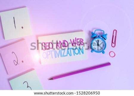 Writing note showing Seo And Web Optimization. Business photo showcasing Search Engine Keywording Marketing Strategies Blank notepads marker rubber band alarm clock clip colored background.