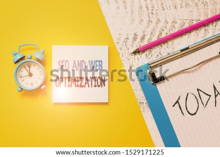 Writing note showing Seo And Web Optimization. Business photo showcasing Search Engine Keywording Marketing Strategies Notepad clipboard colored paper sheet alarm clock wooden background.