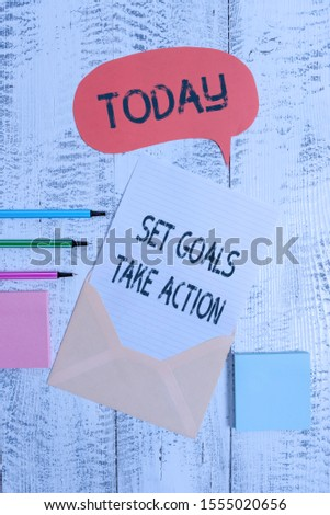 Writing note showing Set Goals Take Action. Business photo showcasing Act on a specific and clearly laid out plans Envelop speech bubble paper sheet ballpoints notepads wooden background.