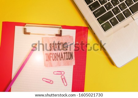 Writing note showing Sharing Information. Business photo showcasing exchange of data between various organizations Laptop clipboard paper sheet clips pencil crushed colored background.