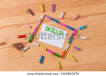 Writing note showing Skills. Business photo showcasing ability do something very well by nature Colored clothespin papers empty reminder wooden floor background office. #1469885876