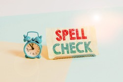 Writing note showing Spell Check. Business photo showcasing to use a computer program to find and correct spelling errors Alarm clock beside a Paper sheet placed on pastel backdrop.