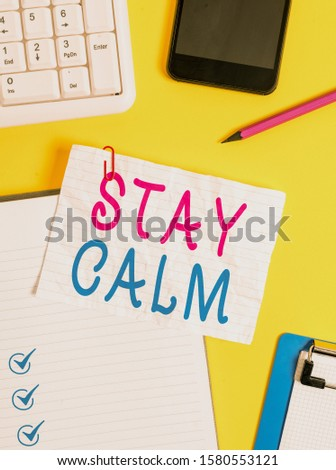 Writing note showing Stay Calm. Business photo showcasing Maintain in a state of motion smoothly even under pressure Crumpled white paper on table paper clips clock mobile and pc keyboard.