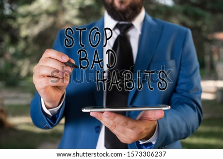 Writing note showing Stop Bad Habits. Business photo showcasing asking someone to quit doing non good actions and altitude Businessman in blue suite stands with mobile phone in hands.