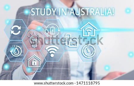 Writing note showing Study In Australia. Business photo showcasing going into foreign country order complete your studies Female human wear formal work suit presenting smart device.
