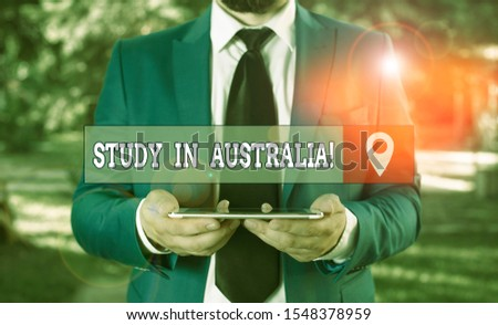 Writing note showing Study In Australia. Business photo showcasing going into foreign country order complete your studies Businessman in blue suite with a tie holds lap top in hands.