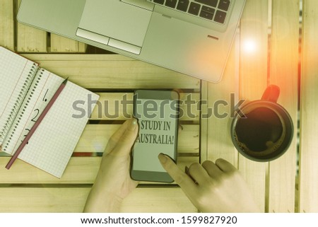 Writing note showing Study In Australia. Business photo showcasing going into foreign country order complete your studies woman with laptop smartphone and office supplies technology.