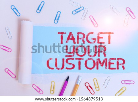 Writing note showing Target Your Customer. Business photo showcasing Tailor Marketing Pitch Defining Potential Consumers Stationary and torn cardboard placed above plain pastel table backdrop.